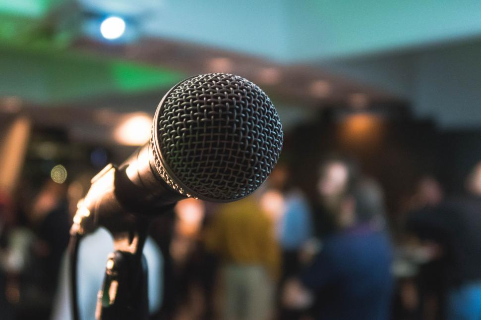 Microphone in front of blurry audience signaling fear of public speaking